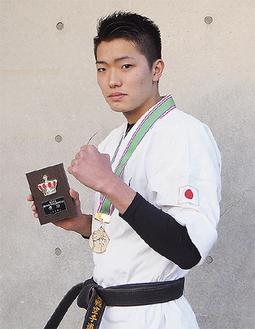 メダルと盾を手にする堀内さん