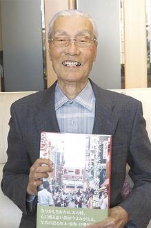 完成した本を手に笑顔の渋谷利雄さん