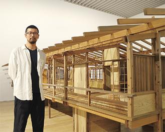 展示設営中の丹下健三邸再現模型の横に立つ野口さん=4月12日・森美術館