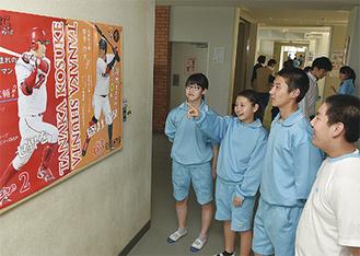 田中広輔選手と俊太選手の母校でもある依知中学校の掲示のようす。球界で活躍する先輩のポスターを眺める生徒らも笑顔。同校では職員室前、体育館前、校長室に掲示されている