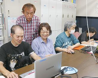 パソコンを使ってリハビリをする利用者を見守る本間施設長(写真奥)。センターではセラピー犬も活躍する
