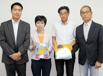 寄贈した日産の黒須課長(左)と本を手にする幼稚園協会の会員