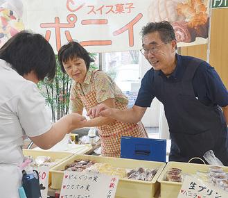 湘南厚木病院でのロビー販売は慣れたものの岸田さん。お客さんとの会話は冗談の連発=7月6日・同病院