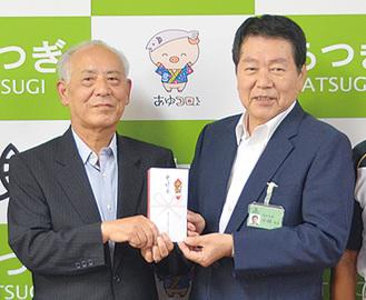 寄付金を手渡す野澤会長(左)