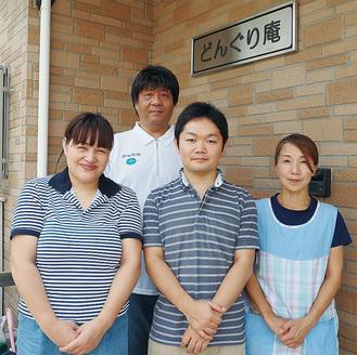光の射しこむホーム玄関で施設長の住谷さん(後列)とスタッフに囲まれる久保田さん(前列中央)