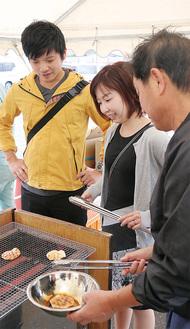 社員(右手前)に手ほどきを受け、煎餅をひっくり返す参加者