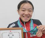 銅メダルと賞状を手に笑顔の田原さん