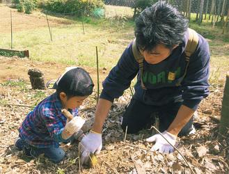 汗をかきながらタケノコを掘る親子。市内外から訪れた参加者らが収穫したタケノコは、薪をくべて灰汁を抜き、スープに調理。また焼き芋や焼きマシュマロのほか、花祭りが近い事から甘茶なども楽しんだ