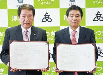 協定を交わした小巻社長(右)と小林市長