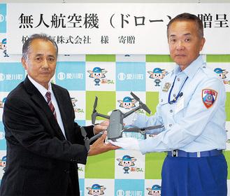 贈呈式で石川消防長(右)にドローンを手渡す柏木代表取締役(左)
