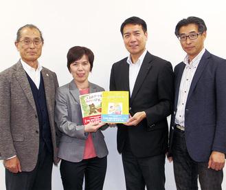 日産の黒須課長(中央右)から協会に絵本が手渡された