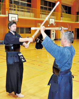 竹村指導部長を相手に、竹刀の振り方を練習するハルさん