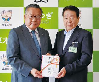 寄付金は昼間社長(左)から小林常良厚木市長(右)へ手渡された