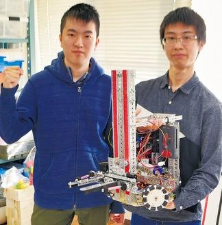 技能五輪のために製作したロボットを持つ小川さん(右)と藤田さん