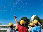 舞い上がる風船に手を振る児童ら