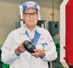 歯車を手にする大久保社長。厚木市上依知には第二工場も所有する。従業員数505人