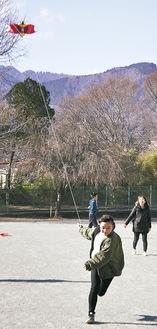 せんみ凧を空高く揚げようと校庭を駆け抜ける児童