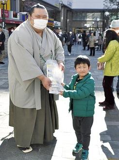 「相撲が大好き」という少年に啓発チラシを手渡す千代丸関