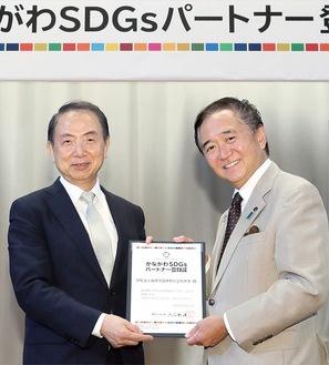 黒岩祐治知事から登録証を受け取る小宮学長(左)