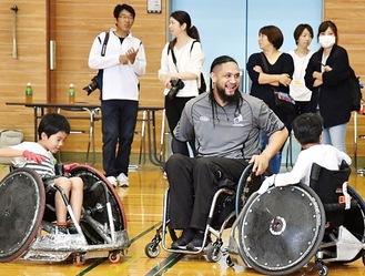相川小で児童と交流するNZ車いすラグビー選手(厚木市提供)