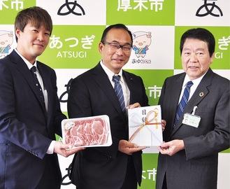 あつぎ豚を手渡す臼井代表(中央)