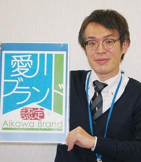 愛川ブランドのロゴを手にする町職員