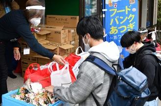 スタッフから袋詰めの食品を受け取る学生