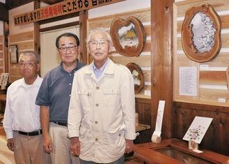 作品の前に立つ(右から)又村さん、森林組合の杉山さん、コーナー開設に協力した関庄治さん
