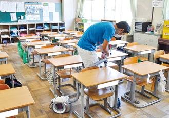 児童が下校すると、机や椅子の消毒を行い、その後、教室の掃除機掛けをする教諭(6月29日/南毛利小学校)