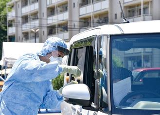 車の中の受診者に検査を説明する医師=厚木市提供