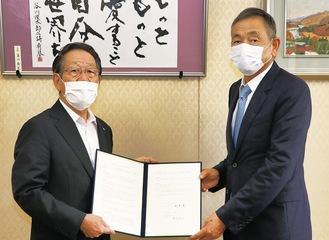 協定書を手にする篠崎代表取締役社長(右)と小野澤町長