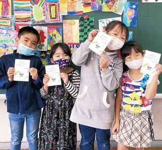 小野澤町長からのメッセージが添えられたクオカードを手にする児童