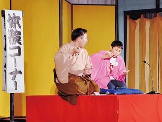 高座でそばをすする仕草を実演する男子児童(右)