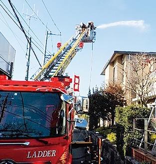 火事を想定して消防車両から放水する消防隊員