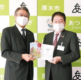 DVDを手渡す平井理事長(左)と小林市長