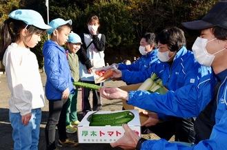 厚木産の農産物を手渡した会員たち