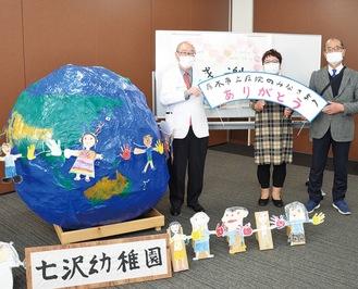 子どもたちが作った地球のオブジェ。(右から)小島校長、仲園長。長谷川病院長