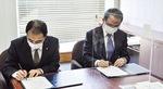 協定書に署名をする小宮学長(右)と村上校長