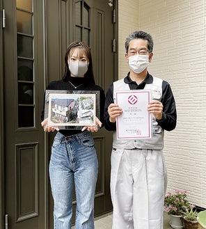 こだわりの玄関前で(株)アイビーリフォーム小口哲司社長(右)と渡部遥さん