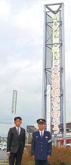 寄贈された懸垂幕と真田会長(左)、押部署長