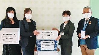マスクを渡す川上恵美幹事(中左)と落合朱美事業委員長(左)、受け取る児相職員