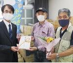 日本フルハーフ(株)では災害備蓄品を寄付。部屋に入りきらないほどの大量の物資となった。目録を手渡す高橋取締役厚木工場長(左)