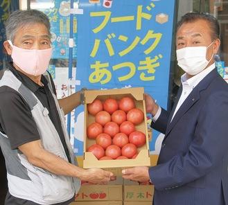 厚木トマトを手渡すJAあつぎの高橋常務理事(右)