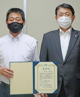賞状を手にする山口さん(左)と佐藤照明教育長