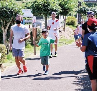 聖火トーチを繋いで走る児童ら