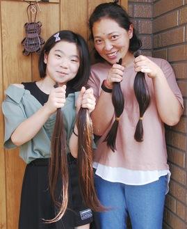カットした髪を手にする田崎直子さん(右)・理紗さん(左)。これから自分たちで髪を送る準備をするという