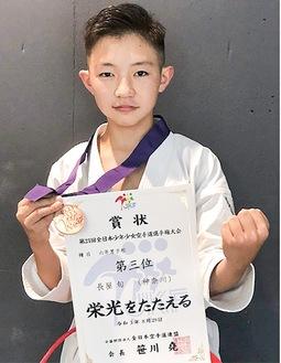メダルと賞状を手にする長屋選手