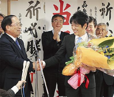 堀江則之選対本部長(左)と握手する義家氏