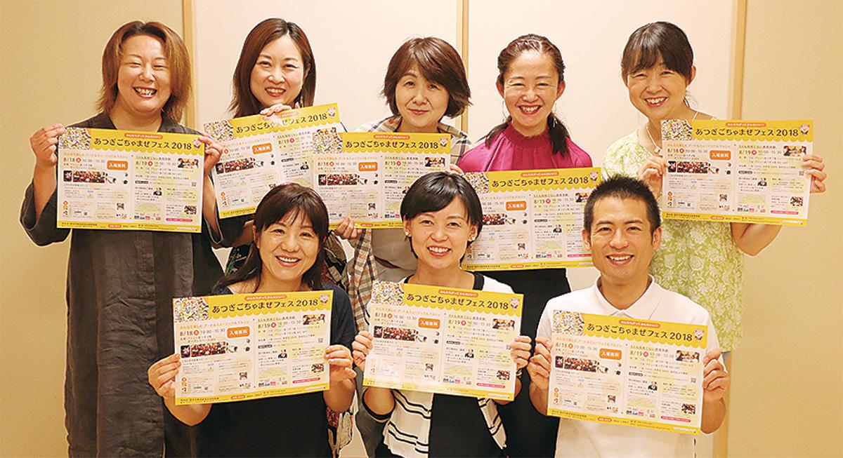 ポスターを手にする実行委員会のメンバー。前列中央が小野さん
