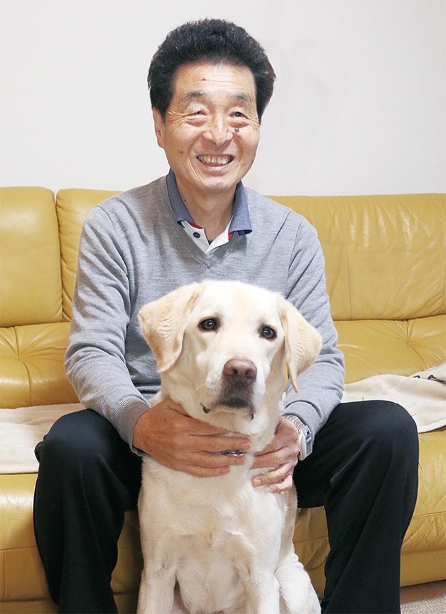 代表の水野さんとアイメイト(盲導犬)のピーター君。水野さんは噺家として寄席にも出演する